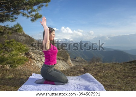beautiful Young woman exercises yoga in the mountains