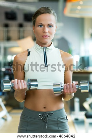 Beautiful young woman exercising with dumbbells in the gym - stock photo