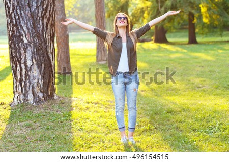 Beautiful young woman expressing freedom outdoors with her arms outstretched.