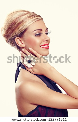 beautiful young woman face close-up wearing bright pink lipstick and long false eyelashes and a large flower cocktail ring in vintage colour - stock photo