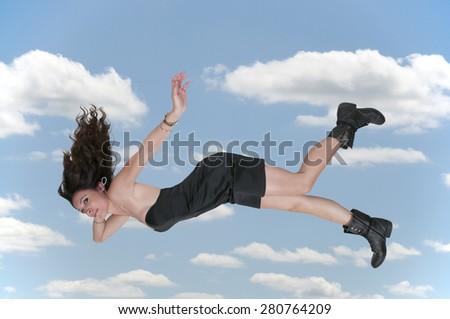 Beautiful young woman falling through the sky - stock photo