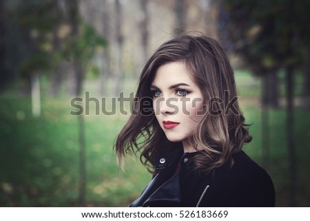 Beautiful Young Woman Fashion Model Walking in the Park. Outdoors Portrait