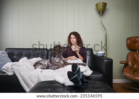 beautiful young woman feeding a dog popcorn - stock photo