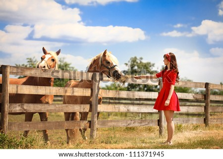 Beautiful young woman feeding her horse
