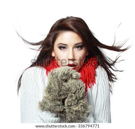 beautiful young woman feeling cold wind in winter hearing warm closthes and fur gloves isolated over white - stock photo