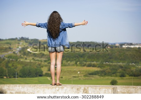 Beautiful young woman feeling the summer breeze and enjoying the vacations - stock photo