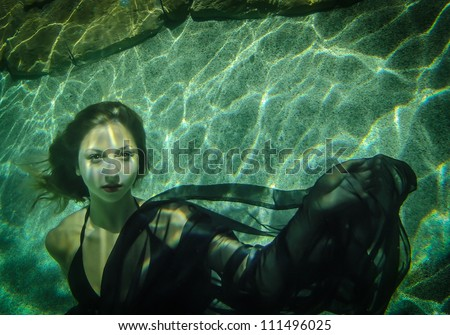 Beautiful young woman floating underwater in a black dress - stock photo