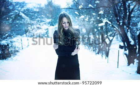 beautiful young woman freezes in the winter suburb - stock photo