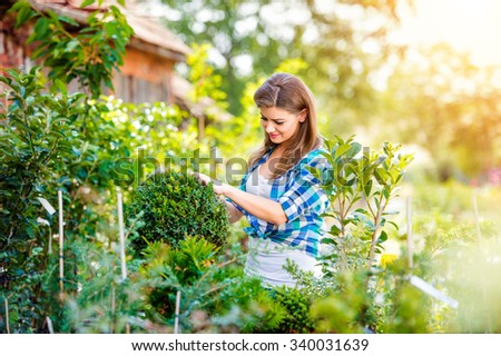 Beautiful young woman gardening outside in summer nature - stock photo