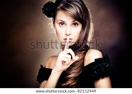beautiful young woman gesturing silence, studio shot