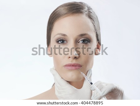 Beautiful young woman gets beauty injection. Isolated over white background.  - stock photo