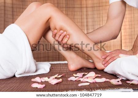 Beautiful young woman getting feet massage treatment at spa - stock photo