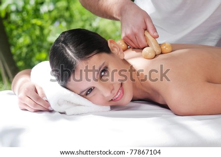 Beautiful young woman getting massage by a therapist - stock photo
