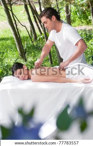 Beautiful young woman getting massage from a therapist - stock photo