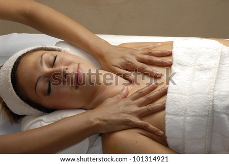 Beautiful young woman getting massage treatment at beauty salon.