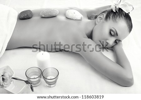 Beautiful young woman getting spa massage. Black and white - stock photo