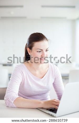 Beautiful young woman/girl/student in classroom/high school library with laptop computer on the desk looking happy/relaxed (color toned image, shallow DOF) - stock photo