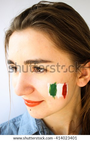 Beautiful young woman girl with painted italian flag on face, football fan supporter - stock photo