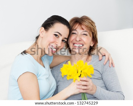 Beautiful young woman giving to her mother flowers for Mother's Day. - stock photo