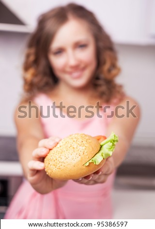 beautiful young woman giving us a sandwich, focus on the sandwich