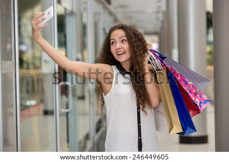 beautiful young woman goes shopping using a smartphone with a shopping bags in the mall - stock photo