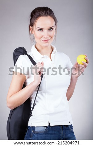 Beautiful young woman going for tennis with rocket and ball - stock photo