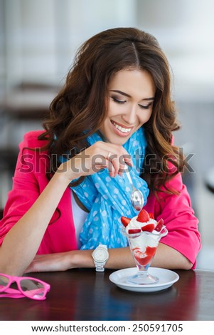 Beautiful young woman happy smiling & looking at camera sitting in restaurant or cafe and eating ice cream closeup portrait, smiling and looking in camera. young beautiful woman eating a dessert - stock photo
