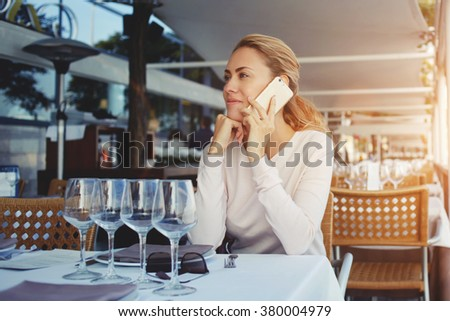 Beautiful young woman have nice conversation on cell telephone during work break in modern restaurant, hipster girl talking on mobile phone with her boyfriend while sitting in cozy cafe in sunny day - stock photo