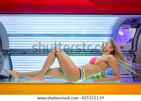 Beautiful young woman have tanning skin treatment in modern solarium - stock photo