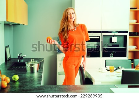 Beautiful young woman having a dinner at a kitchen at home. Home interior. - stock photo