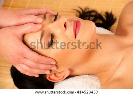 Beautiful young woman having a face massage in wellness studio - spa - stock photo