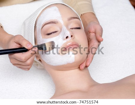 Beautiful young woman having a facial cosmetic mask at spa salon - stock photo