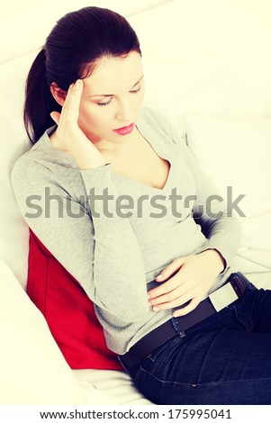 Beautiful young woman having a headache, sitting on a couch and holding her hand next to the head.