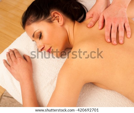 Beautiful young woman having a rejuvenating massage in a wellness studio - spa - stock photo