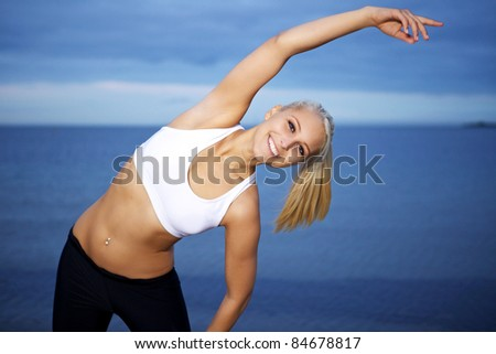 Beautiful young woman having a stretching workout. - stock photo