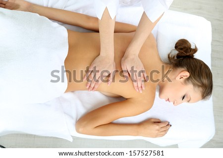Beautiful young woman having back massage close up - stock photo