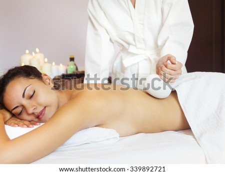 Beautiful young woman having back massage with pouch of rice. Close up