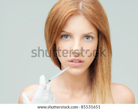 beautiful young woman having colagen injection lips - stock photo