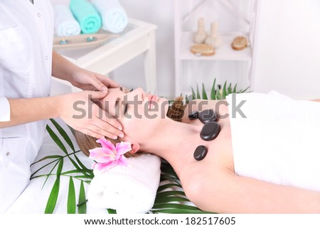 Beautiful young woman having  head and stone massage in spa salon - stock photo