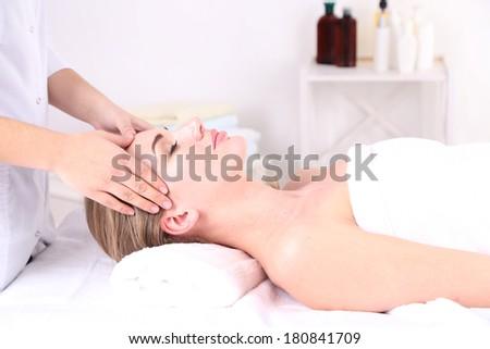 Beautiful young woman having head massage in spa salon - stock photo