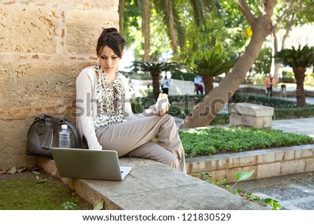 Beautiful young woman having her lunch break in a city park, using a laptop computer and holding a sandwich in her hand. - stock photo