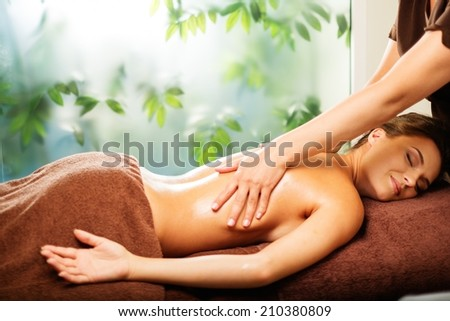 Beautiful young woman having massage in a spa salon - stock photo