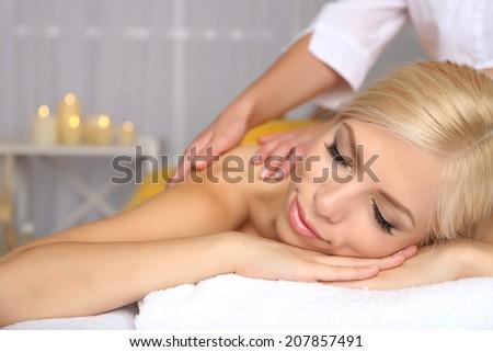 Beautiful young woman having massage in spa salon - stock photo