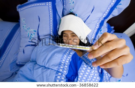 beautiful young woman having over 39?C /102?F fever. focus on thermometer with a shallow dept of field. - stock photo