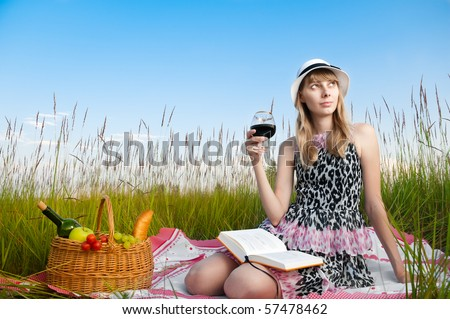 beautiful young woman having picnic on meadow, reading book, smiling and drinking wine. Looking away from camera, blue cloudy sky in background