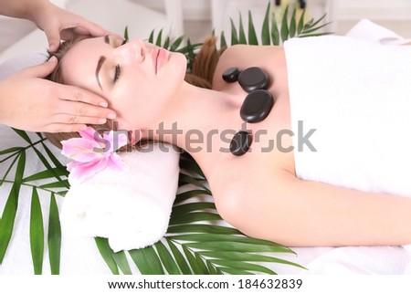 Beautiful young woman having stone massage in spa salon - stock photo