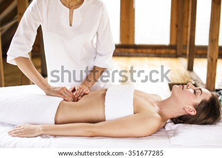 Beautiful young woman having visceral massage in spa center - stock photo