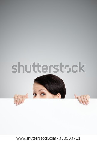 Beautiful young woman hides behind a huge sheet of white cardboard, isolated on grey - stock photo