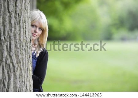 beautiful young woman hiding behind a tree - stock photo