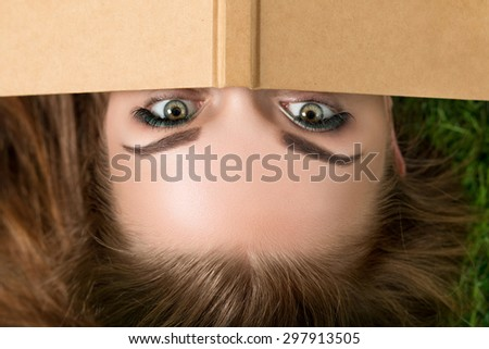 Beautiful young woman hiding her face behind book cover. Summertime, leisure and education concept Top view - stock photo